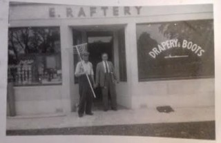 Two gentlemen in front of Rafter's shop, one holding what looks like a rake | Lilian Higgins