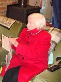 Sheilah Cangley, reading paper, wearing red coat. Australia, 2016 | Courtesy of Sheilah Cangley