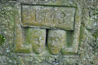 Pair of ornamental stops re set into the graveyard wall.  | Christy Cunniffe
