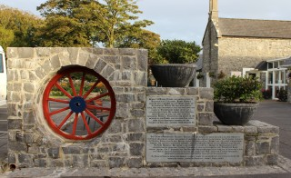 Broken Chariot Wheel with plaque containing history of Toghermore House. | Photo: Bernadette Forde