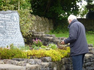 Sylvester Cassidy sprinkling some clay that had been gathered from each unmarked children's burial ground in the oarish, at the base of the new memorial stone. | B. Connolly