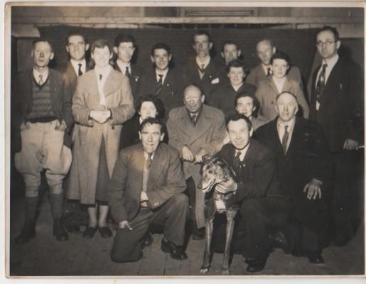 1958: The Cobwebs Glory presented by the Milltown Gaelic Athletic Association at the Ballinrobe Drama Festival Back Row: Michael Connolly (Drim), Joe Kirrane (Kilgevrin), John Varley (Knock), Johnny Hession (Russelstown), James Francis Slattery (Milltown), Jimmy Walsh (Liskeavy) Second Row: Jim Brennan (Liskeavy), Mary Varley (Kneeling), Mary Coyne (Milltown), Joe Farrell (Ballymary), Mary Fleming (Liskeavy), Willie Burke (Milltown), Standing 2nd Row: Una Connolly, Nora McCormack (Liskeavy), Luke Hehir (Kilgevrin) Front Row: John Walsh (Liskeavy), Patrick Hehir (Kilgevrin) with greyhound (Dancing Bobbie) | Frank Glynn