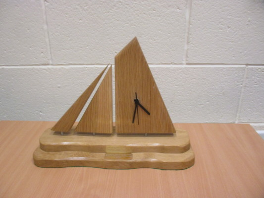'This handmade Galway Hooker Sailboat Clock is made with solid Oak and has a beeswax finish. The sails also swivel to make use of the best light and orientation in the room. The sculpture sits on a double plinth representing the rugged Irish coastline. The clock is battery operated and is a silent movement with black hands.' (Ref: Awards Programme) | Hand sculpted by Kevin McDonagh of Carraroe Crafts