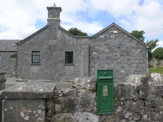 Limestone faced Scoil Naomh Bride, Tullach Ui Chadhain, built in 1862, with a post 2000 annex on right. A Victorian cast-iron post box (with VR initials) is set into the front wall. Royal Mail post boxes were painted bronze-green from 1859 until 1874 when the red colour became standard. Post boxes in Ireland were painted green after the Irish Free State was established in 1922. | Ronan Hennessy