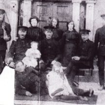 Photo taken outside RIC barracks.  Identity of officer on either side is unknown.  Back Row l-r: Mrs. Bridget Cain, her daughters Agnes and Kathleen Cain (mother of Dom Dunleavy, present owner of Barbersfort House), Front row l-r: Sergeant Dominick Keane who is holding his grandson Dominic and in front is an R.I.C. officer whose identity is also unknown with Rose Keane to the right | Killererin - A Parish History P 486