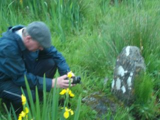 Des Doherty photographing the marker for the well, yellow orchids surround him in long grass | B. Doherty 2016