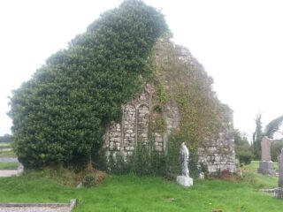 ivy covered gable partially covering tracery window | B. Doherty 2020