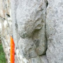 Late medieval carved head with flowing hair on the archway of church door   B. Doherty 2020