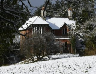 Red brick house with snow covering the roof and garden to the front | Frank Nevin