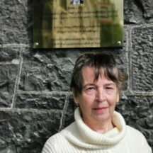 Maureen, Michael Johns wife standing beside the plaque | M. Kenny