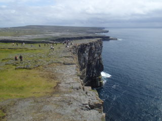 Sea cliffs on the southern edge of Inish Mor on Oileann Arainn.  The cliffs expose beds of limestone and bear testament to the ferocious power of the Atlantic waves.  The ice sculpted, bare limestone pavement of the rest of the island terrain is seen in the distance.