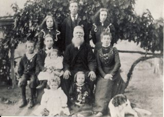 Mary (née Blackmore) and Henry Bradbury, with some of their children and grandchildren, in about 1903. (Back row, left to right)  Henrietta (later Spry); Harry (a.k.a. Henry junior); Sarah (l. Fitzgerald); (middle row) William; Mary (née Blackmore) holding baby Mabel (l. Clayton); Henry senior; Elizabeth Jennings (née Bradbury); (front row) Eva (l. O'Brien) and Hilda (l. Gwynne).